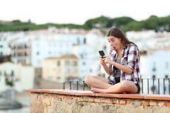 Shocked teenage girl checking phone on vacation stock image