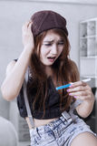 Shocked teenage girl with pregnancy test Stock Photo