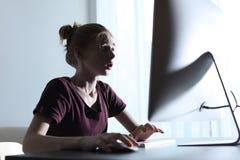 Shocked teenage girl using computer at table. Danger of internet. Shocked teenage girl using computer at table indoors. Danger of internet royalty free stock photo