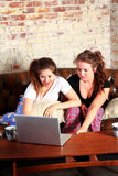 Shocked teens while networking. Two brunette teenage girls sitting on a sofa in their pajamas looking shocked while looking at a computer Royalty Free Stock Images