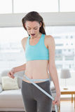 Shocked toned woman measuring waist in fitness studio Stock Image