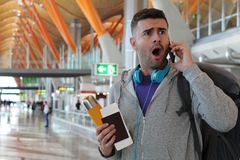 Shocked traveler getting an unexpected phone call.  Stock Image