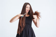 Shocked unhappy woman trimming split ends of hair with scissors Royalty Free Stock Image