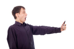 Shocked weirdo man looking at cellphone. Shocked weirdo nerd man looking at cellphone, isolated on white background Stock Photo