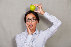 Shocked well-dressed female with apple on head Stock Images