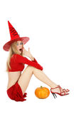 Shocked witch. Beautiful blond girl with long legs in costume of Halloween witch sitting on white background with shocked expression Royalty Free Stock Images