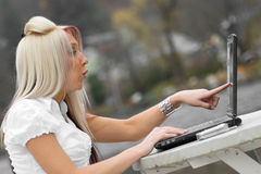 Shocked Woman. A beautiful young blonde woman points to her laptop screen in amazement. It looks as if she is seeing something offensive stock photos
