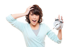 Shocked woman with alarm clock. Portrait of shocked woman with alarm clock over white background Stock Photography