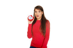Shocked woman with alarm clock. Stock Image