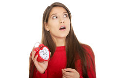 Shocked woman with alarm clock. Stock Photo