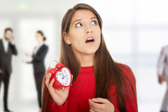 Shocked woman with alarm clock. Stock Photos