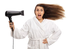 Shocked woman in a bathrobe drying her hair with a hairdryer Stock Image
