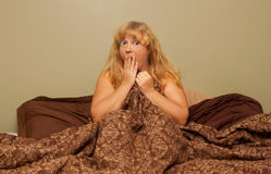 Shocked woman in bed Stock Photos
