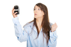 Shocked woman in big shirt holding alarm clock. Stock Photography