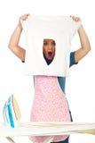Shocked woman with burned iron shirt stock image