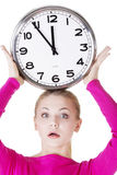 Shocked woman with clock. Portrait of shocked woman with clock over white background Stock Photography
