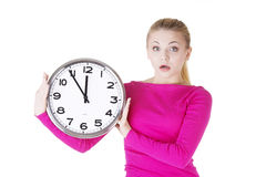 Shocked woman with clock. Portrait of shocked woman with clock over white background Stock Photos