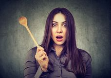 Shocked woman with cooking spoon. Young housewife holding wooden spoon and looking with great surprise and shock at camera on gray background stock image
