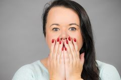 Shocked woman covering her mouth with hand. Shocked surprised plus size adult woman covering her mouth with hand, being terrified or scared. Female seeing royalty free stock photography