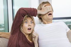 Shocked woman covering man's eyes while watching TV at home Royalty Free Stock Images