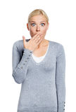 Shocked woman covers her mouth with hand. Shocked woman covers her opened mouth with hand, isolated on white Royalty Free Stock Image