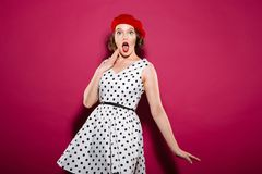 Shocked woman in dress looking at camera with open mouth. Shocked ginger woman in dress looking at the camera with open mouth over pink background Stock Image