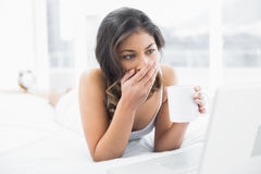 Shocked woman drinking coffee while using laptop in bed Stock Images