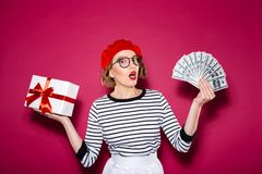Shocked woman in eyeglasses choosing between gift box and money. Shocked ginger woman in eyeglasses choosing between gift box and money while looking at the Royalty Free Stock Photos