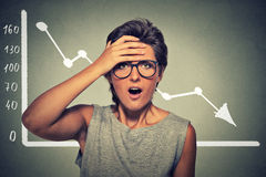Shocked woman with financial market chart graphic going down. Shocked emotional young woman desperate with financial market chart graphic going down on gray stock photo