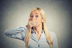 Shocked woman forced to cover her mouth with hand Royalty Free Stock Images