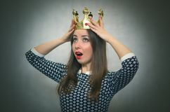Shocked woman with golden crown. First place concept. Surprised and excited woman girl is holding in hands a golden crown award above her head isolated on gray Royalty Free Stock Photos