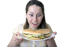 Shocked woman with hamburgers. Young smiling woman with wide eyes, looking at a plate of three cheeseburgers held in her hands.  Isolated on a white background Stock Images