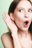 Shocked woman with hand to ear listening secret Royalty Free Stock Photos