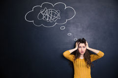 Shocked woman with hands on head standing against chalkboard background Stock Photography