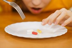 Shocked woman having pills on plate. Shocked woman taking pill, eating one medicine from plate. Healthcare and medical condition concept Stock Images