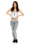 Shocked woman holding big clock. Royalty Free Stock Image