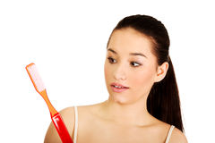 Shocked woman holding big toothbrush. Stock Images