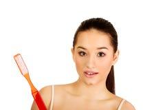 Shocked woman holding big toothbrush. Stock Image