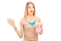 Shocked woman holding a box of popcorn Royalty Free Stock Images