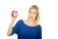 Shocked woman holding a clock. Stock Images