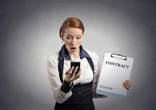 Shocked woman holding contract document looking at smartphone Royalty Free Stock Photos