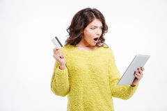Shocked woman holding credit card and tablet computer Royalty Free Stock Photo
