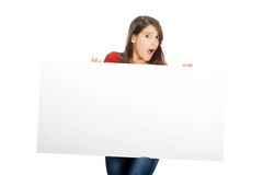 Shocked woman holding empty banner. Royalty Free Stock Photography
