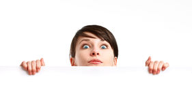 Shocked woman holding an empty sheet of paper. Shocked woman holding an empty banner - blank sheet of paper - on white background royalty free stock image