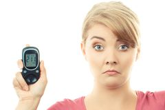 Shocked woman holding glucose meter with bad result of sugar level. Shocked and worry woman holding glucometer with bad result of measurement sugar level royalty free stock photos
