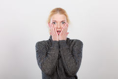 Shocked woman holding hands on face Stock Images