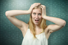 Shocked Woman Holding her Head Looking at Camera Royalty Free Stock Photography
