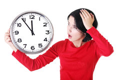 Shocked woman holding office clock. Isolated on white bacvkground Stock Photo