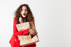 Shocked woman holding paper shopping bags and looking at camera Stock Photo
