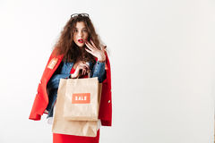 Shocked woman holding paper shopping bags and looking at camera Royalty Free Stock Photos
